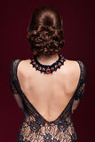 Young beautiful woman in black dress from back side on marsala c Royalty Free Stock Photos