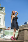 Young beautiful woman in black dress posing outdoors in sunny we Stock Images