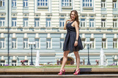 Young beautiful woman in black dress posing outdoors in sunny we Royalty Free Stock Photo