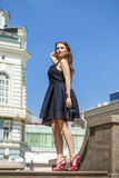 Young beautiful woman in black dress posing outdoors in sunny we Stock Photos