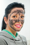 Young beautiful woman with black facial beauty mask Stock Image