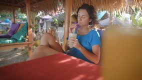 Young beautiful woman with black hair, dressed in a blue dress sitting on a sandy beach on a chair under a straw. Umbrella and thoughtfully drinking a milkshake stock footage
