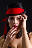 Woman in black hat with red scarf Royalty Free Stock Images