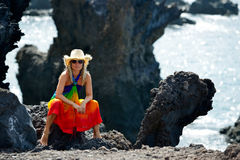 Young beautiful woman between black rocks Royalty Free Stock Photo