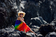 Young beautiful woman between black rocks on the beach Stock Photography