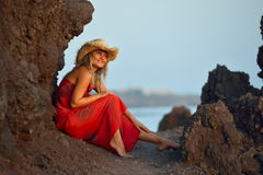 Young beautiful woman between black rocks on the beach Royalty Free Stock Photography