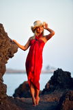 Young beautiful woman between black rocks on the beach in summer Royalty Free Stock Photos