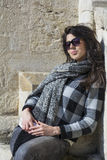 Young beautiful woman with black scarf against stone wall Royalty Free Stock Photography