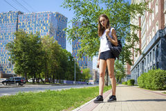 Young beautiful woman in black short walking on the summer stree. Portrait in full growth, young beautiful brunette woman in black short walking on the street Stock Photos
