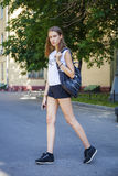 Young beautiful woman in black short walking on the summer stree. Portrait in full growth, young beautiful brunette woman in black short walking on the street Royalty Free Stock Photography