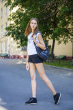 Young beautiful woman in black short walking on the summer stree. Portrait in full growth, young beautiful brunette woman in black short walking on the street Stock Images