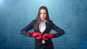 Young beautiful woman in black suit and white shirt standing in combat pose with red boxing gloves. Business concept. Royalty Free Stock Photos