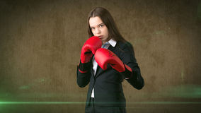 Young beautiful woman in black suit and white shirt standing in combat pose with red boxing gloves. Business concept. Stock Photography