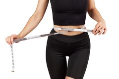 A young beautiful woman in a black tracksuit measures the volume of the thigh with a centimeter tape, isolate on a white backgroun