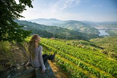 Young beautiful woman with blond dreadlocks meets sunset on the viewing point of Douro Valley, Portugal. Top view of river, and the vineyards are on a hills Stock Image