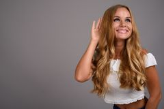 Young beautiful woman with blond hair against gray background. Studio shot of young beautiful woman with blond hair against gray background royalty free stock photo