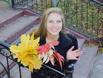 Young beautiful the woman the blonde with blue eyes holds a bouquet of autumn yellow leaves in hand. The woman is happy, she smiles. The woman is on a ladder Stock Photography