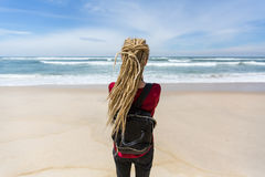 Young beautiful woman with blonde dreadlocks standing by the ocean. Stock Photography