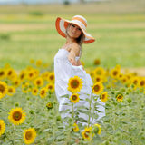 Young beautiful woman on blooming sunflower field Royalty Free Stock Image