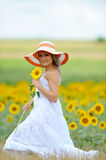 Young beautiful woman on blooming sunflower field Royalty Free Stock Photos