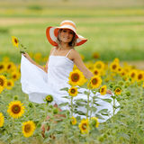 Young beautiful woman on blooming sunflower field in summer Royalty Free Stock Images