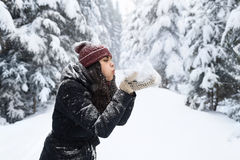 Young Beautiful Woman Blow Snow Hands In Winter Forest Girl Outdoors Walking Snowy White Park. Wear Warm Clothes Stock Images