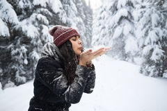 Young Beautiful Woman Blow Snow Hands In Winter Forest Girl Outdoors Walking Snowy White Park. Wear Warm Clothes Royalty Free Stock Image