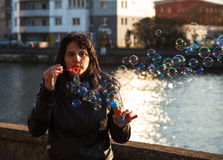 Young beautiful woman blows bubbles Stock Images