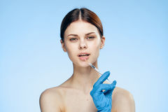 Young beautiful woman on a blue background holds a syringe, medicine, plastic surgery, rubber gloves Stock Photos
