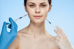 Young beautiful woman on a blue background injects botox, plastic surgery stock photography
