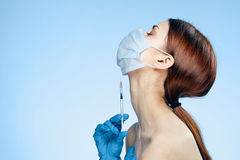 Young beautiful woman on a blue background in a medical mask and gloves holds a syringe, medicine, doctor royalty free stock image