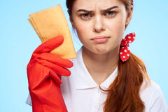 Young beautiful woman on a blue background in rubber gloves, cleaning, housework.  Royalty Free Stock Images
