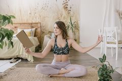 Young beautiful woman in blue bra and pink pants is doing yoga exercise and reading in the bedroom. Young beautiful woman in blue bra and pink pants is doing Royalty Free Stock Photography