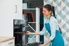 Young beautiful woman in blue dickey puts baking pan into oven. Young beautiful woman in blue dickey puts baking pan into the oven. Female pastry chef cooking Royalty Free Stock Image