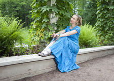 The young beautiful woman in a blue dress in the arbor twined a green bindweed Royalty Free Stock Photos