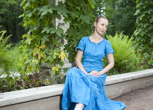 Young beautiful woman in a blue dress in the arbor twined a green bindweed Stock Images