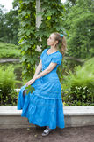 Young beautiful woman in a blue dress in the arbor twined a green bindweed Royalty Free Stock Photo