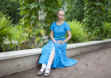 Young beautiful woman in a blue dress in the arbor twined a green bindweed. The young beautiful woman in a blue dress in the arbor twined a green bindweed Royalty Free Stock Photos