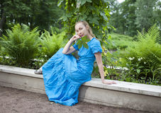 Young beautiful woman in a blue dress in the arbor twined a green bindweed Stock Photos