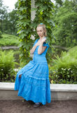 Young beautiful woman in a blue dress in the arbor twined a green bindweed Royalty Free Stock Image