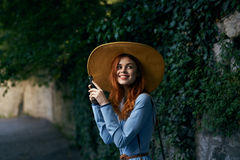Young beautiful woman in a blue dress and hat makes photos on her phone outdoors in the city royalty free stock photography