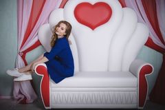 Young beautiful woman in blue dress posing on the sofa. Young beautiful woman in blue dress posing on white sofa Royalty Free Stock Photo