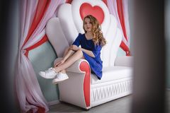 Young beautiful woman in blue dress posing on the sofa. Young beautiful woman in blue dress posing on white sofa Stock Photography