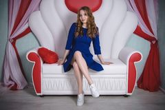 Young beautiful woman in blue dress posing on the sofa. Young beautiful woman in blue dress posing on white sofa Royalty Free Stock Photography