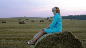 Young beautiful woman in blue dress sitting on a haystack in a large field. stock footage