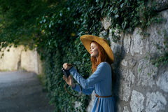 Young beautiful woman in a blue dress walking along the street with a camera Stock Photography