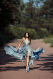 Young beautiful woman blue dress walking path in park. stock photography