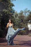 Young beautiful woman blue dress walking path in park. royalty free stock photography