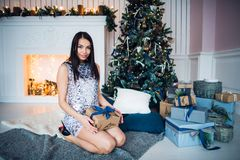 Young beautiful woman in blue elegant evening dress sitting on floor near christmas tree and presents on a new year eve stock image