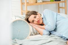 Woman sleeping with clock on the bed stock images
